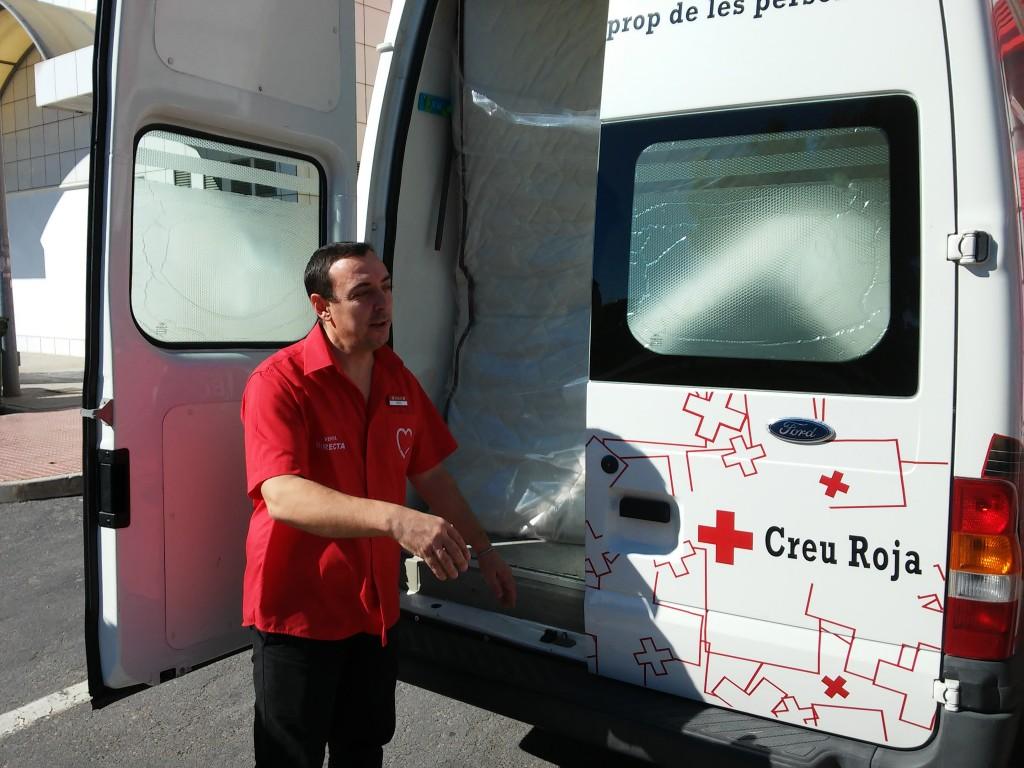 Trabajador de Muebles BOOM ayuda a cargar el mobiliario en una furgoneta de la Cruz Roja
